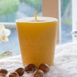 large beeswax votive candle at the window with orchid