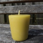 large beeswax votive candle on the bench