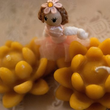 two beeswax lilly candles with a doll